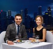 在餐馆的微笑的夫妇吃主菜 免版税库存照片