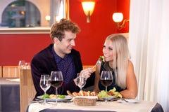 在餐馆的相当微笑的年轻恋人日期 库存照片