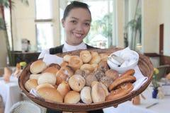 在餐馆等候人员上添面包 图库摄影