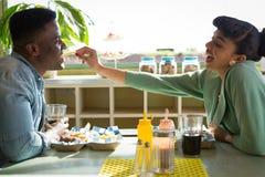 在餐馆结合一起坐,当妇女哺养的食物时 库存照片