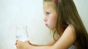 在餐馆,在桌上,与泡影的孩子女孩饮用的碳酸盐矿物水从玻璃 画象 股票视频