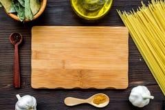在餐馆 嘲笑为菜单或食谱 在成份附近的木切板 未加工的面团,油,大蒜,在黑暗的香料 免版税库存图片
