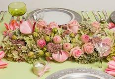 在饭桌上的欢乐花的布置 库存图片