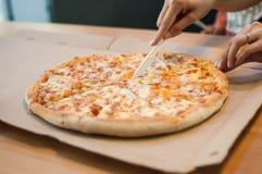在饭桌的一整个四奶酪披萨 免版税库存照片