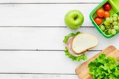 在饭盒的健康食物在学校白色桌背景顶视图大模型的晚餐的 免版税图库摄影