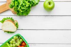 在饭盒的健康食物在学校白色桌背景顶视图大模型的晚餐的 库存照片