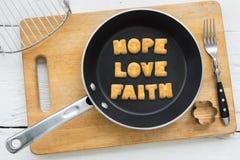 在饼干上写字措辞希望爱信念和烹调设备 免版税图库摄影