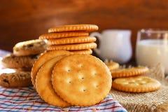 在饼干薄脆饼干涂黄油,并且牛奶在餐巾和木bac设定了 库存图片