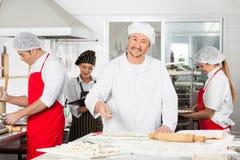 洒在馄饨面团的微笑的厨师面粉  库存图片