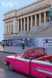 在首都大厦前面的老明亮的桃红色敞篷车古巴汽车 库存照片