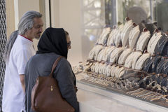在首饰店柜台前面的回教夫妇与石榴石珠宝 库存照片