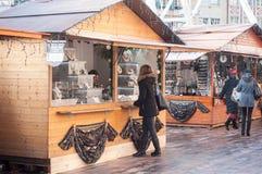 在首饰立场前面的妇女在圣诞节市场上 库存照片