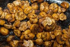 在香料和油的煮熟的小油煎的蘑菇一半在开胃黑暗的背景 免版税库存照片