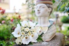 在香槟玻璃附近的婚姻的白玫瑰花束 免版税库存图片
