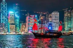 在香港地平线背景的破烂物航行与从横跨维多利亚港的Tsim Tsa Tsui江边观看的城市光 免版税库存图片