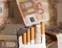 在香烟上花的金钱 图库摄影