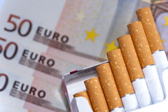 在香烟上花的金钱 库存照片