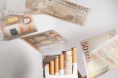 在香烟上花的金钱 免版税库存照片