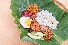 在香蕉叶子的传统nasi lemak烹调有炸鸡的 免版税库存照片
