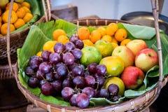 在香蕉叶子的许多果子在竹篮子 免版税库存图片