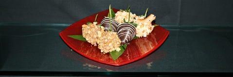 在马卡达姆坚果蘸的草莓前面射击巧克力和椰子在一块红色玻璃板剥落有黑背景 库存图片