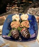 在马卡达姆坚果蘸的草莓特写镜头射击巧克力和椰子在一块蓝色淡光玻璃板剥落 图库摄影