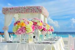 在马尔代夫海滩设定的花卉表焦点 免版税库存图片