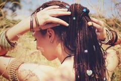 在马尾辫和装饰的被分类的小珠会集的美好的少妇佩带的dreadlocks发型 库存照片