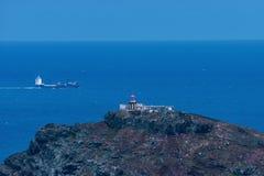 在马德拉海岛,集装箱船上的灯塔在背景中 库存照片