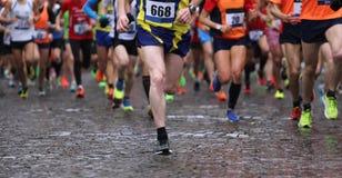 在马拉松期间的赛跑者,当下雨时 库存照片