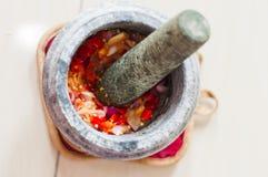 在马来语的灰浆和杵或者lesung batu用被击碎的辣椒、油煎的青葱和虾酱混合在一起 免版税库存照片
