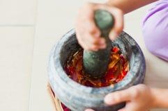 在马来语的灰浆和杵或者lesung batu用被击碎的辣椒、油煎的青葱和虾酱混合在一起 免版税库存图片