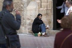 在马略卡供以人员乞求在一个教会门 库存照片