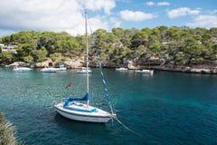 在马略卡的岩石小海湾有船的在阳光下 免版税图库摄影