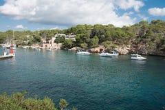 在马略卡的岩石小海湾有船的在阳光下 库存图片