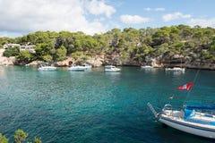 在马略卡的岩石小海湾有船的在阳光下 免版税库存图片