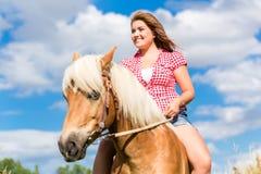 在马的妇女骑马在草甸 免版税库存照片