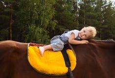 在马的愉快的赤足婴孩骑马没有马鞍 免版税图库摄影