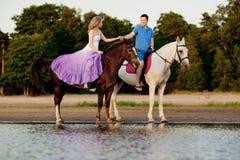 在马背上两个车手在海滩的日落 恋人乘驾hors 免版税图库摄影