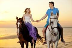 在马背上两个车手在海滩的日落 恋人乘驾hors 库存照片