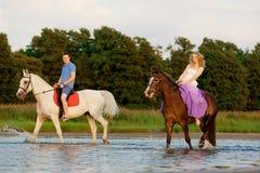 在马背上两个车手在海滩的日落 恋人乘驾hors 图库摄影