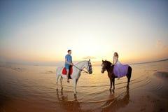 在马背上两个车手在海滩的日落 恋人乘驾hors 免版税库存照片