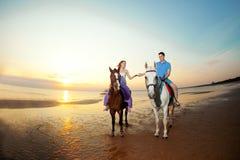 在马背上两个车手在海滩的日落 恋人乘驾hors 库存图片