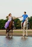 在马背上两个车手在海滩的日落 恋人乘驾hors 免版税库存图片