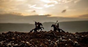 在马背上两个骑士之间的马上枪术比赛 在背景的日落 选择聚焦 库存照片