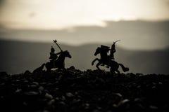 在马背上两个骑士之间的马上枪术比赛 在背景的日落 选择聚焦 免版税库存图片