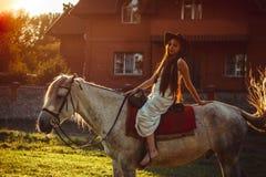 在马背上女孩在日落 免版税库存图片