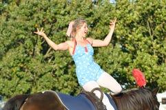 在马背上挥动东英吉利骑马公平的女孩拥挤 免版税库存照片