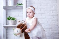 在马背上白色豪华的礼服的小女孩 免版税库存图片