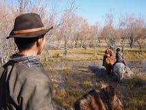 在马背上穿过河的蒙古牧民 免版税图库摄影